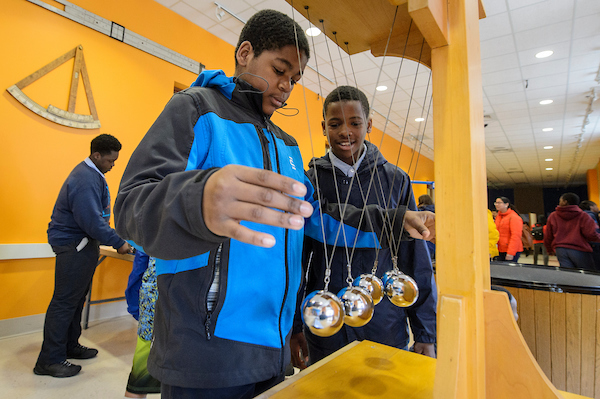 Two students play with Newton's Cradle