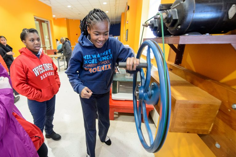 Two young students play with a wheel crank