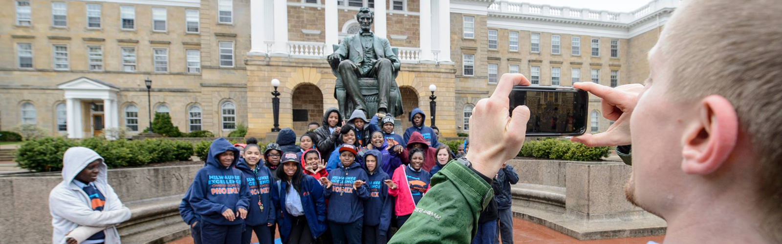 Milwaukee Excellence Charter School students have their photo taken in front of Abe at UW–Madison